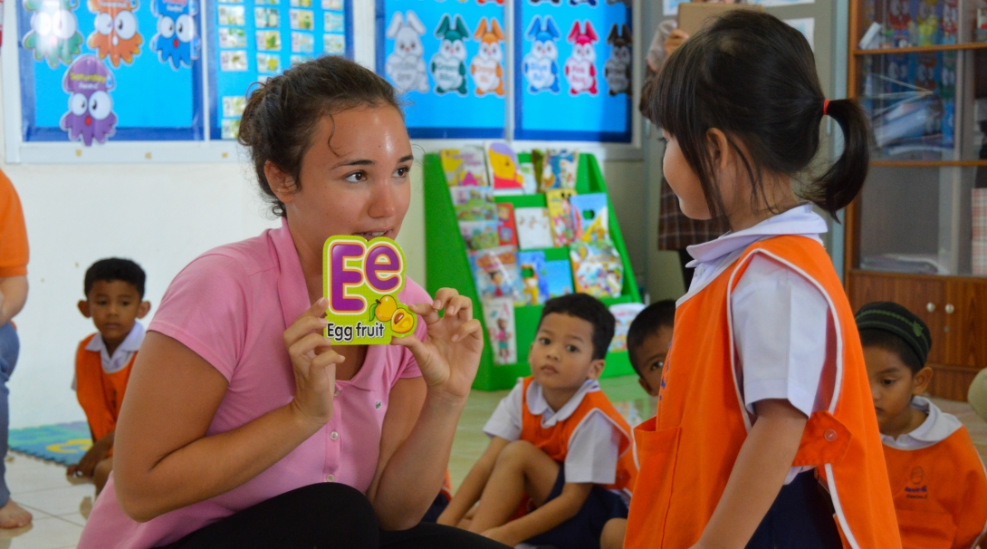 A volunteer teaches the alphabet to children at her Projects Abroad placement where no experience is needed to volunteer overseas.